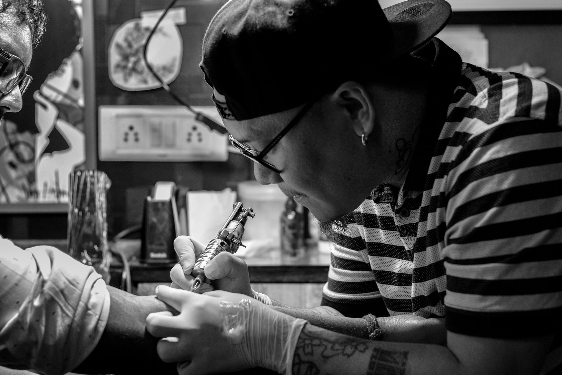 Job Role Image (Tattooist and customer, black and white)